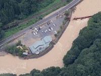 激しい雨で増水した最上小国川。右上は壊れた吊り橋=山形県最上町で2018年8月31日午後1時10分、本社機「希望」から佐々木順一撮影