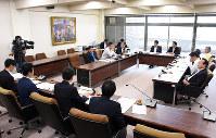 LCC就航に関する支援の概要について報告する高知県職員(左手前)と、質疑する産業振興土木委の委員ら(右奥)=高知県議会第2委員会室で、郡悠介撮影