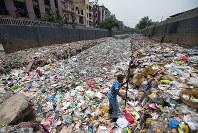 ごみで埋まった水路でプラスチックごみをより分けている男性。ごみはガンジス川を経由してインド洋へ流れる=ニューデリーのタイムール・ナガル地区で2018年6月12日