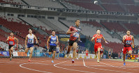 Japan's Asaka Cambridge, center, crosses the finish line for his team's 4x100m relay gold during the athletics competition at the 18th Asian Games in Jakarta, Indonesia, on Aug. 30, 2018. (AP Photo/Bernat Armangue)