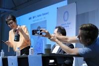 ピースデーの意義を訴え「平和の鐘」のレプリカを打つ高瀬聖子さん(左)を撮影するジェレミー・ギリーさん(右)=東京都千代田区で2018年8月31日、梅村直承撮影