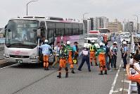東京都と神奈川県境で事故を起こしたバスから乗客を避難させる訓練を行う警察官ら=東京都世田谷区・川崎市高津区境界の新二子橋で2018年9月1日午前9時15分、渡部直樹撮影