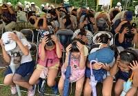 防災総合訓練で自分の身を守る訓練をする参加者ら=大阪府吹田市で2018年9月1日午前10時3分、小松雄介撮影