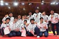 【アジア大会・柔道】柔道混合団体で優勝し、金メダルを手に笑顔の日本の選手たち=ジャカルタで2018年9月1日、徳野仁子撮影