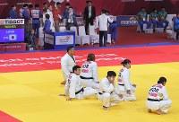 【アジア大会・柔道】柔道混合団体準々決勝、日本の選手たち(左奥)が畳を降りた後も、日本の勝利を不服として畳に座り込む韓国の選手たち=ジャカルタで2018年9月1日、徳野仁子撮影