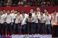 【アジア大会・柔道】柔道混合団体で優勝し、金メダルを手に笑顔を見せる日本の選手たち。表彰台が狭く、中央の影浦心は落ちそうに=ジャカルタで2018年9月1日、徳野仁子撮影