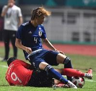 サッカー決勝【日本―韓国】 後半、韓国選手からファウルを受ける板倉滉(上)=インドネシア・ボゴールのパカンサリ競技場で2018年9月1日、宮間俊樹撮影