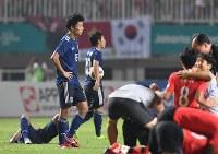 サッカー決勝【日本―韓国】 延長戦で敗れて肩を落とす日本の上田(左から2人目)ら。手前は優勝を喜ぶ韓国の選手ら=インドネシア・ボゴールのパカンサリ競技場で2018年9月1日、宮間俊樹撮影