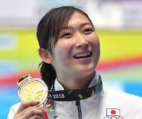 競泳女子50メートル自由形で優勝して6冠を達成し、金メダルを手に笑顔の池江璃花子=ジャカルタで2018年8月24日、徳野仁子撮影