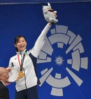 競泳女子50メートル自由形、大会新記録で優勝して6冠を達成し、金メダルを手に笑顔の池江璃花子=ジャカルタで2018年8月24日、徳野仁子撮影