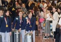 競技を終えて帰国し、出迎えた人たちに手を振る池江璃花子(中央)ら=羽田空港で2018年8月25日、藤井達也撮影