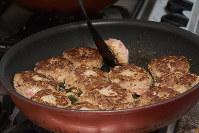 フライパンに油を熱し、ニンニクを炒め、ハンバーグの両面を軽く焼く=根岸基弘撮影