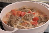 鍋にトマト、水、ニンニクとハンバーグを入れて火を付け、コンソメやケチャップで調味する=根岸基弘撮影
