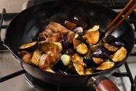 バルサミコ酢を軽く煮詰め、揚げたナスと焼いた豚肉を加え混ぜる=根岸基弘撮影