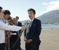 鹿児島で桜島を背景にして出馬表明した首相。NHKドラマ「西郷どん」を意識しての演出とみられる=鹿児島県垂水市の海潟漁港で8月26日、新開良一撮影