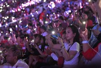 Spectators wait for the start of the Asian Games closing ceremony while using the lights of their cell phones at Gelora Bung Karno Stadium in Jakarta on Sept. 2, 2018. (Mainichi)
