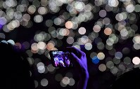 A spectator takes a commemorative photograph with a smartphone at the Asian Games closing ceremony at Gelora Bung Karno Stadium in Jakarta on Sept. 2, 2018. (Mainichi)