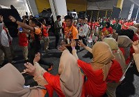 Volunteer staff members bid farewell to athletes after the Asian Games closing ceremony at Gelora Bung Karno Stadium in Jakarta on Sept. 2, 2018. (Mainichi)
