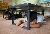 防災の日に行われた地震・津波避難訓練で、学童保育教室の机の下に身を隠す子供たち=岩手県釜石市で2018年9月1日午前8時、小川昌宏撮影