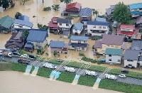 激しい雨で最上小国川が氾濫し、冠水した集落で行われる排水作業=山形県戸沢村で2018年8月31日、本社機「希望」から佐々木順一撮影
