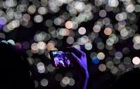 観客のスマートフォンのライトで照らされる閉会式会場を背景に記念撮影する人たち=ジャカルタのブンカルノ競技場で2018年9月2日、宮間俊樹撮影