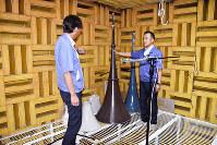 完成したスピーカーの性能などを点検する無響室で従業員と打ち合わせをする福田弘社長(右)=滋賀県日野町で、土居和弘撮影
