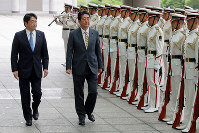 Prime Minister Shinzo Abe, center, is greeted by the honor guard at the Ministry of Defense in Tokyo's Chuo Ward on Sept. 3. At left is Defense Minister Itsunori Onodera. (Mainichi)