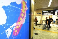 Foreign travelers walk past a monitor showing information about Typhoon Jebi approaching western Japan at JR Osaka Station in Osaka's Kita Ward in the morning of Sept. 4, 2018. (Mainichi)