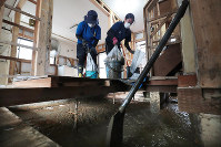Five volunteer students from Kumamoto Gakuen University in southern Japan remove mud at the house of Mitsuko Nakamoto, 71, in the Koyaura district of the town of Saka in Hiroshima Prefecture in western Japan as powerful Typhoon Jebi approaches the region on Sept. 4, 2018. Nakamoto says even a little rainfall has become scary for her. (Mainichi)