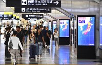 People walk by monitors showing information about approaching Typhoon Jebi at JR Osaka Station in Osaka's Kita Ward in western Japan on Sept. 4, 2018. (Mainichi)