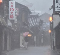 A person walks in strong rain and wind caused by Typhoon Jebi on a street in the historical district of Kyoto's Higashiyama Ward on Sept. 4, 2018. (Mainichi)