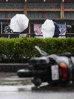 People walk in strong winds and rain due to Typhoon Jebi in the city of Kochi on Sept. 4, 2018. (Mainichi)