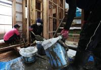 台風21号が近づき雨が降り始める中、坂町小屋浦地区の中本美津子さん(71)方では2カ月前の西日本豪雨で流れ込んだ泥が引かず、熊本学園大のボランティア学生ら5人がスコップとバケツを手に次々と戸外に運び出した。中本さんは「少しでも雨が降ると怖い」と話す=広島県坂町で2018年9月4日午前8時47分、小出洋平撮影