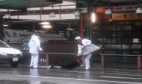 京都・祇園では店舗の屋根の一部が飛ばされ、警察官が撤去に追われた=京都市東山区で2018年9月4日午後2時36分、川平愛撮影