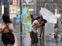 強い雨風でカサを飛ばされそうになりながらも先を急ぐ人たち=大阪市中央区で2018年9月4日午後2時45分、幾島健太郎撮影