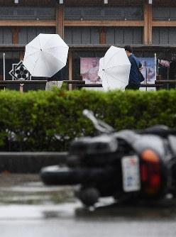 台風の影響による強い風雨の中を歩く人たち=高知市で2018年9月4日午前11時13分、山田尚弘撮影