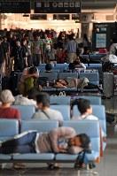 関西国際空港で一夜を過ごし、疲れた様子で横になる人たち=2018年9月5日午前8時23分、小松雄介撮影
