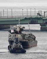 関西国際空港の連絡橋(奥)に衝突して破損したタンカー。連絡橋にも大きな傷が残る=2018年9月5日午前7時55分、本社ヘリから加古信志撮影