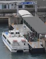 台風から一夜明けて、神戸空港行きの高速船に乗り込む人たち=関西国際空港で2018年9月5日午前8時6分、本社ヘリから加古信志撮影