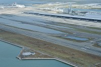 台風21号で崩れた関西国際空港島の護岸(左手前)。中央は高潮で浸水し、まだ水が残る誘導路=2018年9月5日午前8時15分、本社ヘリから加古信志撮影