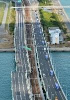 タンカーの衝突で破損した関西国際空港の連絡橋。右は取り残された利用客らを乗せ対岸に向かうバスの列=2018年9月5日午前10時55分、本社ヘリから加古信志撮影