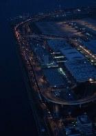 夕闇に浮かび上がった空港島から出発する車のテールランプ(左端)=関西国際空港で2018年9月5日午後6時40分、本社ヘリから加古信志撮影