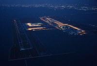 高潮による浸水で閉鎖された関西国際空港。右端はA滑走路。左のB滑走路には滑走路の灯火が光っている=2018年9月5日午後6時46分、本社ヘリから加古信志撮影
