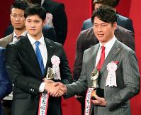 最優秀選手賞に選ばれ、表彰式で握手する日本ハムの大谷翔平(左)と広島の新井貴浩=東京都港区で2016年11月28日午後6時28分、森田剛史撮影