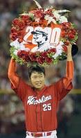 2000安打を達成し、記念のレリーフを掲げて笑顔を見せる広島・新井=神宮球場で2016年4月26日、宮武祐希撮影