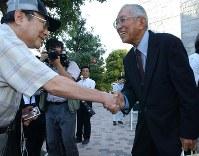違憲判決を勝ち取り、最高裁前で関係者と笑顔で握手する原告団長の高瀬隼彦さん(右)=最高裁前で2005年9月14日、小出洋平撮影