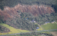 Houses hit by a landslide caused by an earthquake are seen from a Mainichi Shimbun airplane in the town of Atsuma, Hokkaido, on Sept. 6, 2018. (Mainichi)