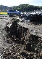 A crack in a farm road caused by an earthquake is seen in the town of Atsuma, Hokkaido, on Sept. 6, 2018. (Mainichi)