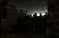 People buy food and necessities at a convenience store in Hakodate Airport during a blackout due to an earthquake, on Sept. 6, 2018 in Hakodate, Hokkaido. (Mainichi)