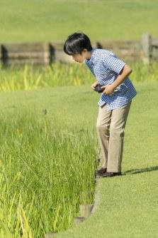 カメラを手にトンボを探す悠仁さま=東京・元赤坂の赤坂御用地で2018年8月10日撮影(宮内庁提供)